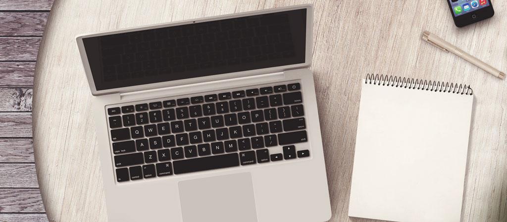 Runder Tisch mit Laptop und Notitzblock
